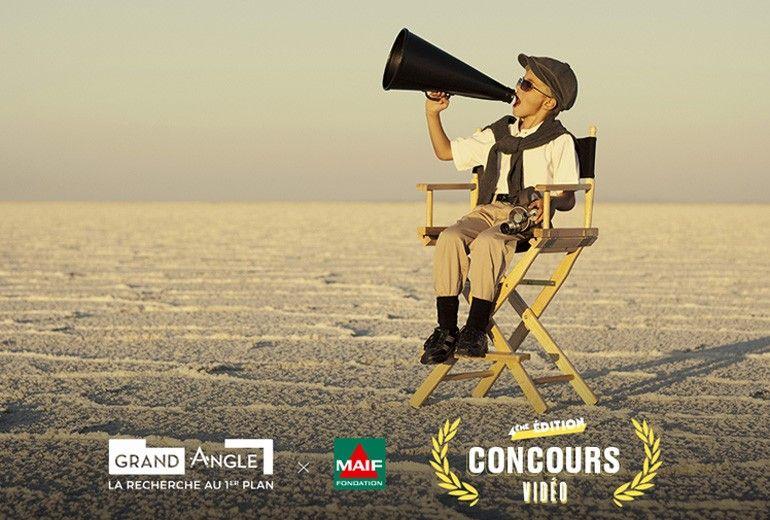 Un jeune garçon assis sur une chaise pliante de tournage en plain désert annonce à la volée dans un porte parole