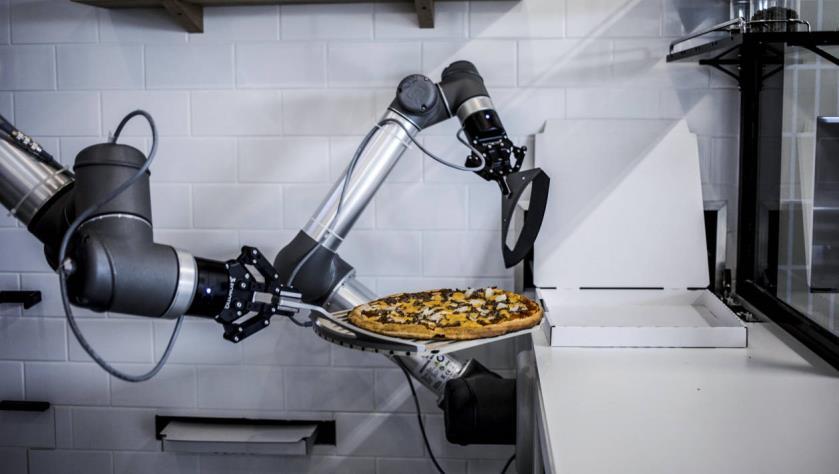 Bras articulé du robot déplace une pizza