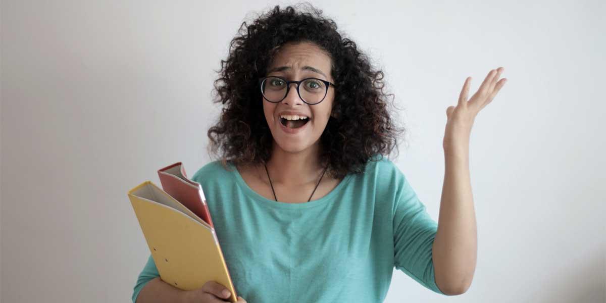 Une femme tiens une pile de dossiers de presse dans ses bras